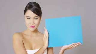 Single beautiful happy young woman looking at blue card that she is holding in her hands