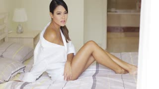 Single beautiful tired woman sitting on top of bed covers in oversized white shirt