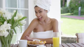Single beautiful woman with body and hair wrapped in white towels holding orange slices while seated at breakfast table outdoors