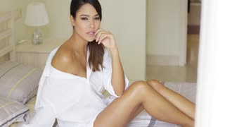 Single beautiful young adult woman with sultry and seductive expression sitting on bed
