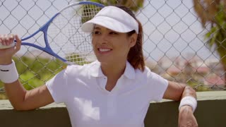 Single beautiful young smiling woman in white hat and blouse leaning on fence with tennis racket held behind her head