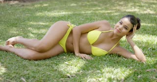 Single beautiful young woman with yellow bikini bathing suit laying down on lawn in partial shade