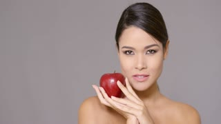Single calm bare shouldered woman holding an large red apple near her cheek over gray background