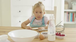 Single cute blond baby baking in a kitchen with large bowl brown egg milk and mixing tools on large wooden counter table