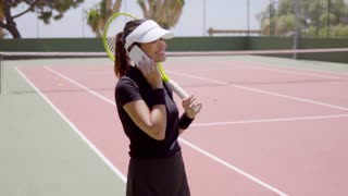 Single female tennis player in black outfit with racquet on phone at empty court outside calling for partner