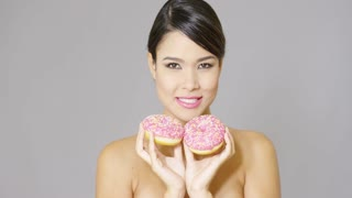 Single gorgeous hungry woman with bare shoulders eating a donut treat covered by strawberry frosting and candy sprinkles