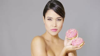 Single gorgeous smiling woman with bare shoulders holding pair of donuts covered by strawberry frosting and candy sprinkles
