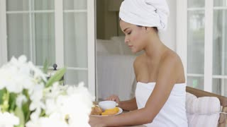 Single gorgeous woman wrapped in towel sitting at table with juice breakfast snack and flower bouquet outside of hotel room