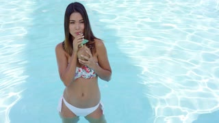 Single gorgeous young woman in bikini partially submerged in water of swimming pool while holding coconut drink