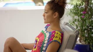 Single woman in colorful knit top sitting in chair