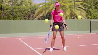 Single woman in pink blouse and sun visor juggling tennis balls on court in tropical area with racket in hand
