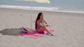 Single woman relaxing under beach umbrella