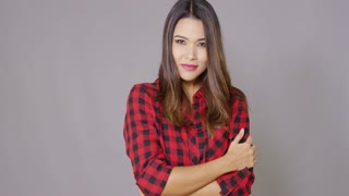 Single woman wearing checkered red and black shirt stands with arms crossed