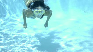 Single woman wearing goggles swimming underwater in pool with copy space surrounding her