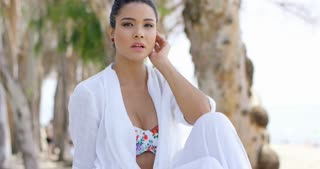 Single young adult woman in white bathing suit robe with confident expression sitting in tropical beach scene