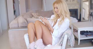Sitting Sensual Woman in White Using her Phone