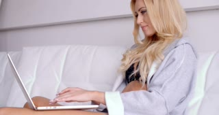 Sitting Woman in an Open Sleep Robe with Laptop