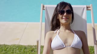 Smiling blissful young woman in a white bikini and sunglasses sunbathing at the edge of a swimming pool in a deck chair