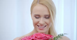 Smiling Blond Woman Smelling Pink Roses