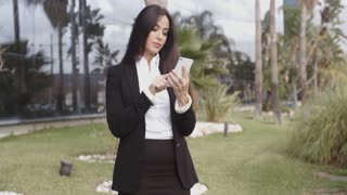 Smiling businesswoman checking her mobile phone