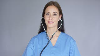 Smiling friendly attractive female nurse or doctor with a stethoscope holding up the disc for the camera head and shoulders in blue scrubs over grey