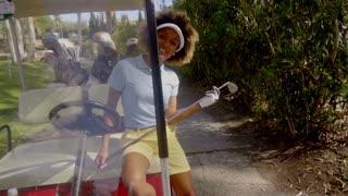 Smiling friendly female golfer in a golf cart