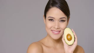 Smiling happy woman holding a halved ripe avocado pear in her hand in a concept of healthy eating and nutrition head and shoulders on grey