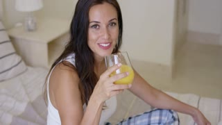 Smiling healthy young woman drinking a glass of freshly squeezed orange juice as she sits on her bed in the morning