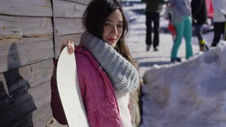 Smiling mixed race girl standing with snowboard in mountains resort. She looking to camra. Wearing woolen scarf and pink jacket.