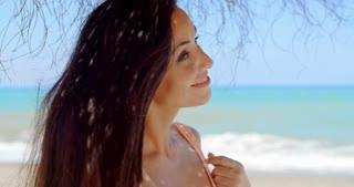 Smiling Pretty Woman Under a Beach Umbrella