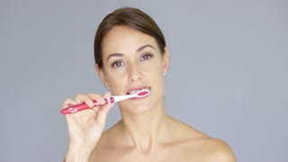 Smiling pretty young woman brushing her teeth with a plastic toothbrush in a dental and oral hygiene concept over a grey background