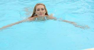 Smiling Woman in White Bikini Emerging at the Pool