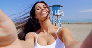 Smiling Woman Taking Self Portrait on Windy Beach