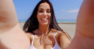 Smiling Woman Taking Self Portrait on Windy Beach