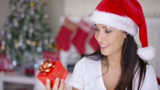 Smiling woman unwrapping her Christmas gift with a look of gleeful anticipation as he celebrates Christmas at home in a red Santa hat