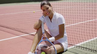 Smiling Woman with Racket Sitting on Tennis Court