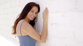 Smiling young brunette presses against white wall