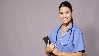 Smiling young female doctor or nurse in scrubs holding a tablet pc as she makes her ward rounds over grey with copy space