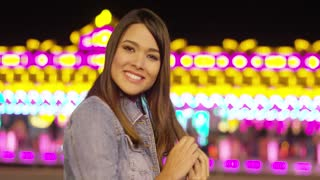 Smiling young woman at a colorful fairground standing in front of a bokeh of bright lights turning to smile at the camera