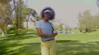 Smiling young woman golfer on a golf course