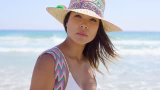 Smiling young woman holding her sunhat in the sea breeze as she walks along a tropical beach on a hot summer day close up portrait