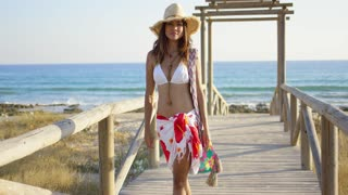 Smiling young woman in a bikini sarong and sunhat walking on a wooden beachfront promenade towards the camera with the sea behind her