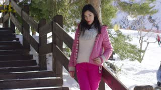 Smiling young woman in pink snowsuit stood relaxing on wooden stairs on skiing holiday