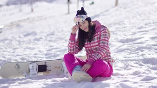 Smiling young woman on winter resort ski slope with snowboard