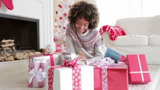 Smiling young woman opening her gifts at Christmas sitting on the floor in front of the tree untying a ribbon on a present