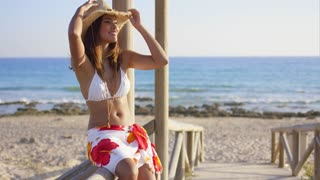 Smiling young woman sitting on a wooden promenade at the beach in a bikini and sarong holding on to her sunhat in the breeze with a smile.