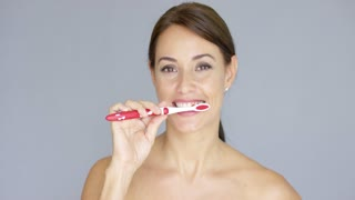 Smiling young woman with sparkling clean white teeth holding a toothbrush in her hand as she runs her tongue over her teeth in a dental and oral hygiene concept.