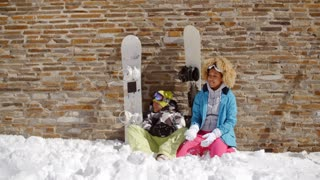 Snowboarding friends sitting in pile of snow