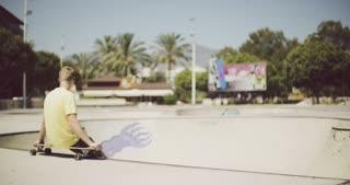 Solitary teenage boy sitting on a longboard