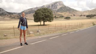Sporty Woman Standing Alone on the Road Ready to Run with Hands Rised on Slow Motion Video